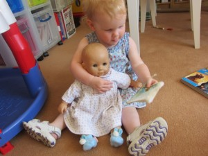"Just in the last week she's started to play with dolls.  Here she is ""reading"" a book to her ""beebee."""