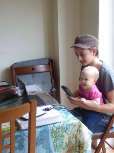 """Jessah gets scooped up by her siblings in all kinds of places around the house.  Here she is """"helping"""" Aliyah do maths."""